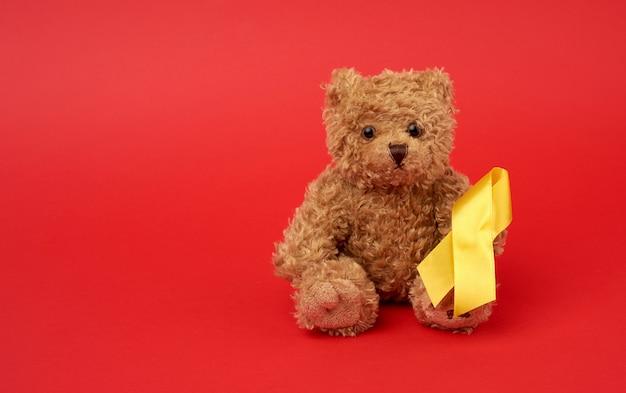 Fofo urso de pelúcia marrom detém uma fita de seda amarela