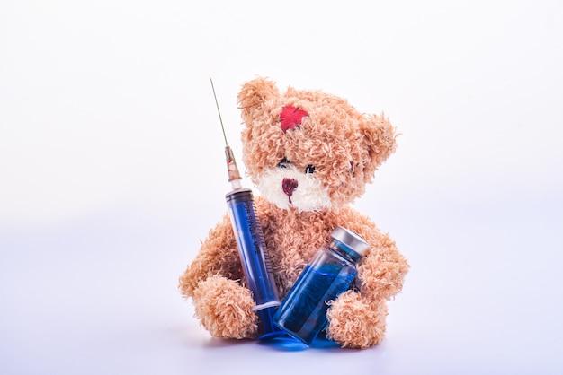 Fofo urso de pelúcia marrom e frasco ou ampolas para injeção e seringa. frasco médico azul e seringa no urso de pelúcia marrom de mãos. ursinho de pelúcia segurando uma seringa e uma ampola. isolado. copie o espaço