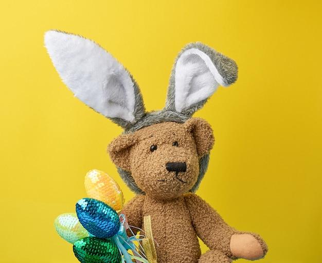 Fofo urso de pelúcia marrom segurando ovos de páscoa coloridos, vestindo uma máscara de coelho com orelhas compridas na cabeça