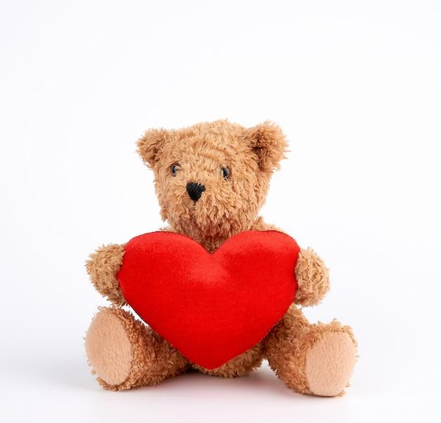 Fofo urso de pelúcia marrom, segurando um coração vermelho grande