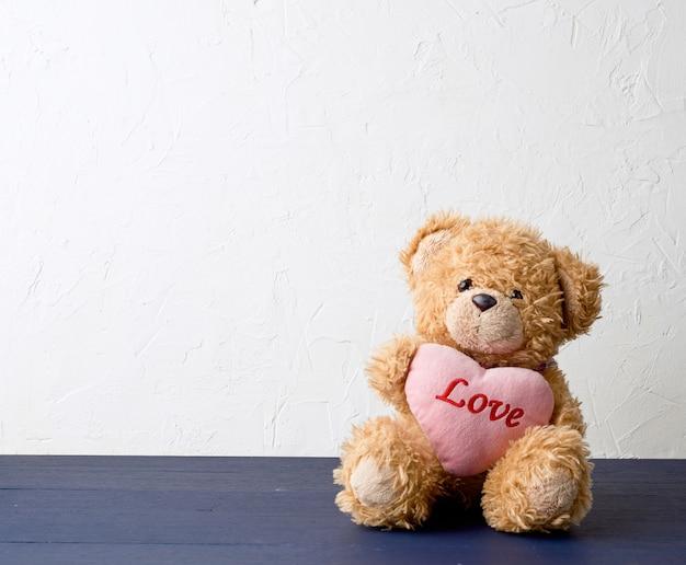 Fofo urso de pelúcia marrom, segurando um grande coração rosa
