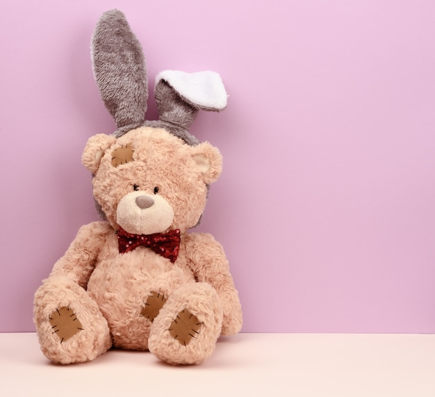 Fofo urso de pelúcia marrom usando uma máscara de coelho com orelhas compridas na cabeça, cartão de páscoa engraçado no feriado