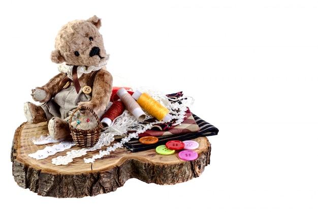 Fofo urso de pelúcia senta-se no tronco. ao lado dele estão pedaços de pano, botões e fios.