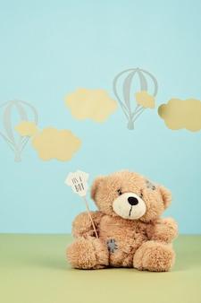 Fofo urso de pelúcia sobre o fundo azul pastel com nuvens e ballons