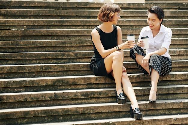 Fofocando empresárias sentado nos degraus