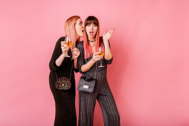 Fofocas meninas com copos de bebidas de álcool posando na parede rosa clara
