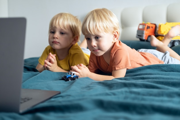 Fofos garotos caucasianos gêmeas usando laptop na cama em casa crianças usando tecnologia