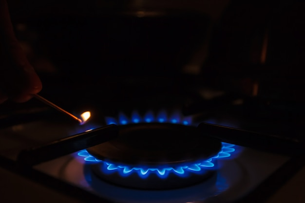 Fogão a gás de cozinha com queima de gás propano de fogo. um homem acendendo o fogão a gás com um fósforo.