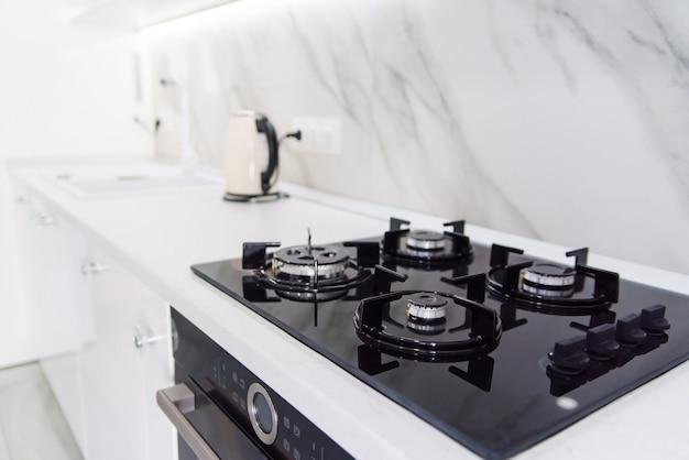 Fogão a gás preto de alta tecnologia moderna com painel sensor no interior brilhante da cozinha com azulejos de mármore branco.