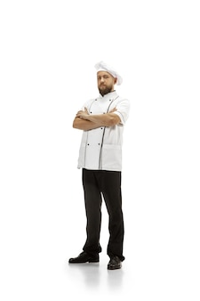 Fogão, chef, padeiro de uniforme isolado no fundo branco do estúdio, gourmet. jovem, o retrato do cozinheiro do restaurante. negócios, foor, ocupação profissional, conceito de emoções. copyspace para anúncio.