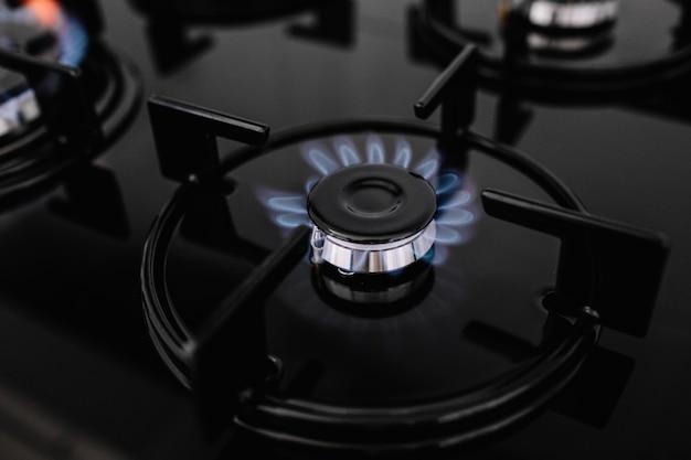 Fogão de cozinha moderna cozinhar com chamas azuis queimando.