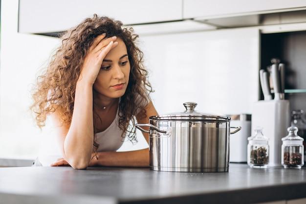 Fogão de mulher fazendo macarrão na cozinha
