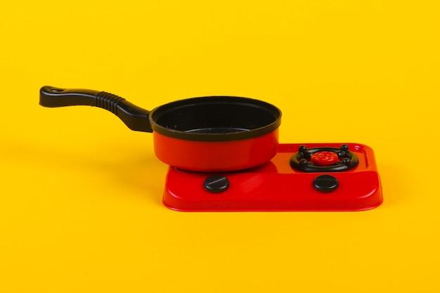 Fogão de plástico de brinquedo com panela em um amarelo. cozinha infantil