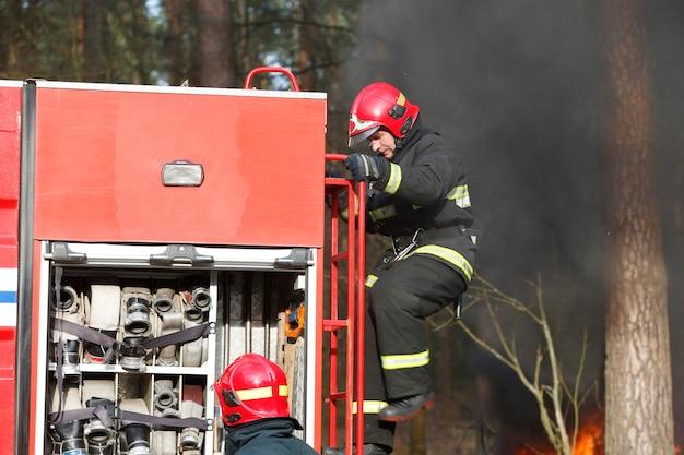 Fogo, bombeiro preparando-se para extinguir um incêndio. apague o fogo. combate o incêndio. incêndios florestais