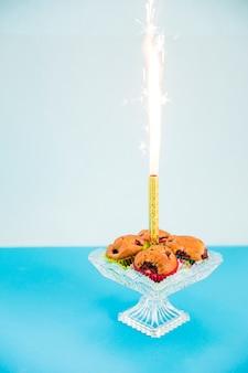 Fogo de artifício brilho no meio do queque na cakestand transparente contra pano de fundo rosa
