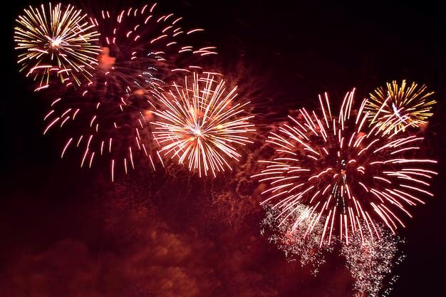 Fogo de artifício colorido da variedade no fundo do céu noturno. saudação com flashes dourados e vermelhos.