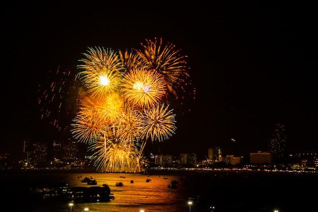 Fogo de artifício colorido sobre fundo de vista cidade à noite para o festival de celebração.