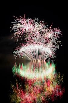 Fogo de artifício. fogos de artifício bonitos e coloridos na superfície da água com um fundo preto limpo. festival de diversão e concurso de bombeiros brno dam - república tcheca.