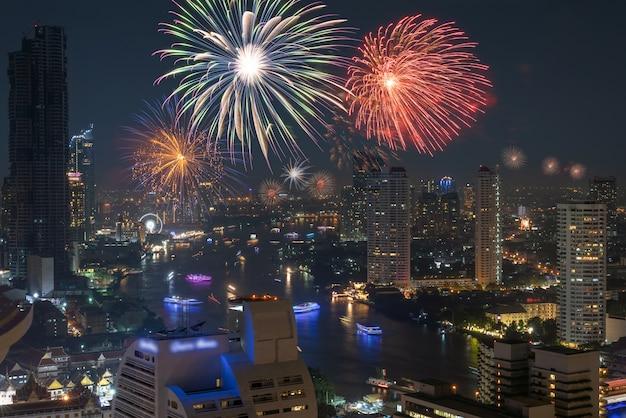 Fogo de artifício multicolor explodindo sobre o lado do rio bangkok cityscape para celebração