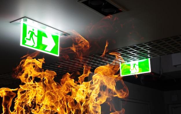Fogo de chama quente e sinal de escape de incêndio verde penduram no teto no escritório à noite