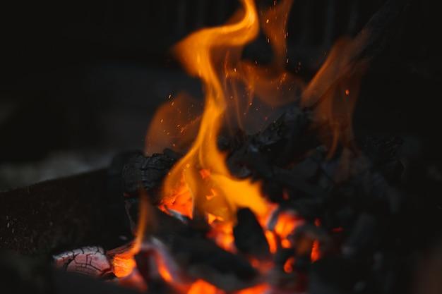 Fogo de um churrasco com cinzas em chamas no ar
