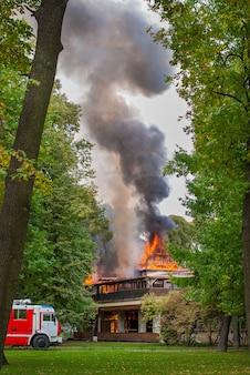 Fogo, desastre, casa está pegando fogo, um carro de bombeiros chegou