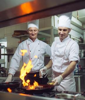 Fogo na cozinha. queima de gás de fogo está cozinhando na panela de ferro, mexa fogo muito quente