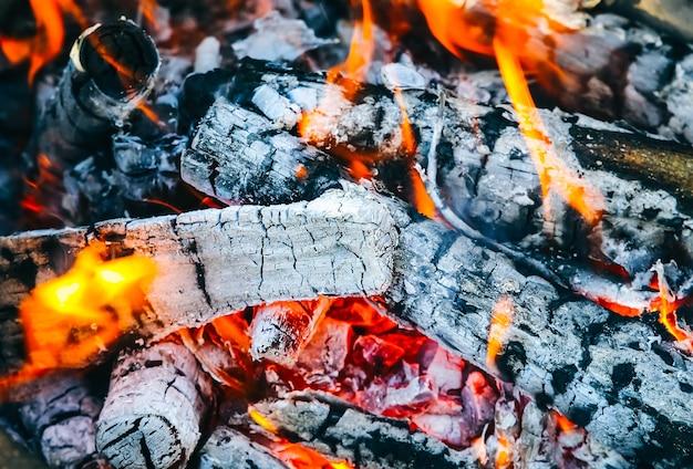 Fogo queimando de madeira. chama real. local para churrasco. combustível natural ecológico. carvão negro.