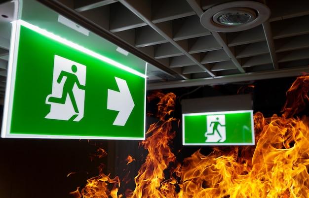 Fogo quente chama e sinal de escape de incêndio verde penduram no teto no escritório à noite.