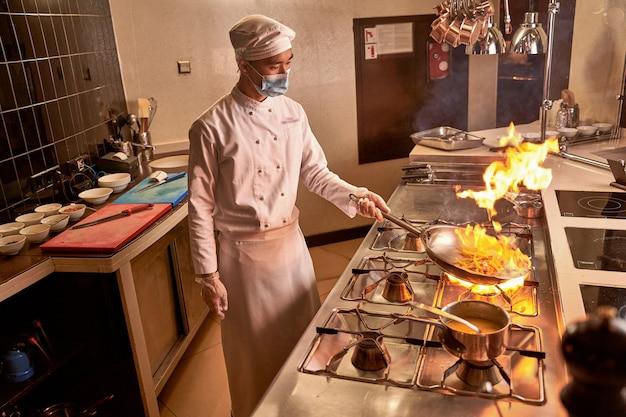 Fogo subindo acima de uma panela com ingredientes de cozinha segurados por um cozinheiro profissional sobre o queimador de um fogão