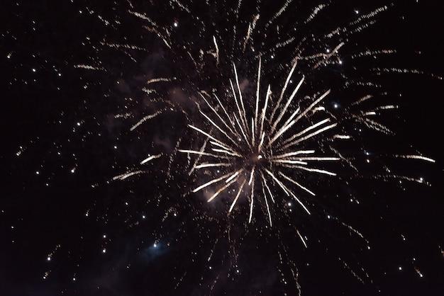 Fogos de artifício amarelos brilhantes, com faíscas e fumaça, contra o fundo do céu noturno. para qualquer propósito.
