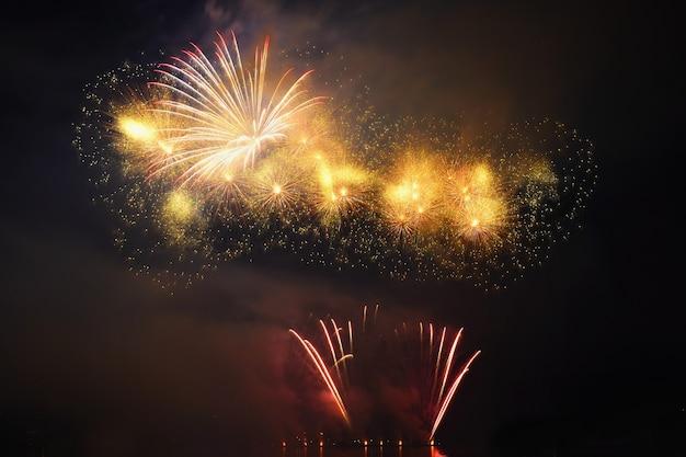 Fogos de artifício bonitos e coloridos na superfície da água com um fundo preto limpo. festival de diversão e concurso internacional de bombeiros de todo o mundo ignis brunensis 2017. represa de brno - república tcheca.