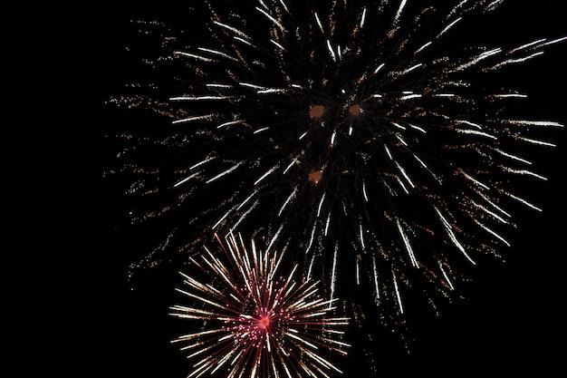 Fogos de artifício brilhantemente coloridos e saudação de várias cores no fundo do céu noturno. foco seletivo