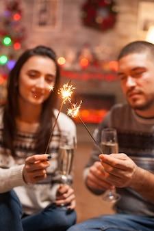 Fogos de artifício brilhantes de mão realizada pelo jovem casal no dia de natal.