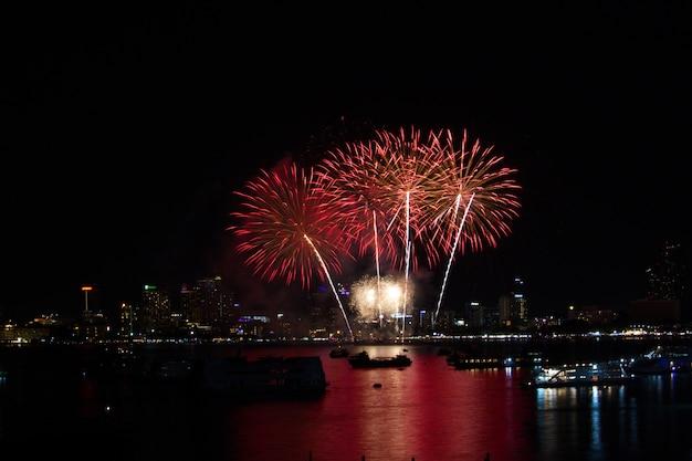 Fogos de artifício cauda longa vermelha na praia e reflexão cor na superfície da água