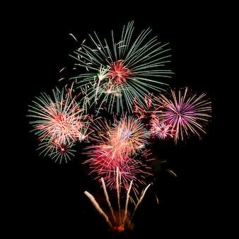 Fogos de artifício coloridos à noite isolado sobre o céu negro escuro
