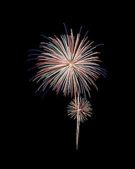 Fogos de artifício coloridos acendem e explodem no céu noturno