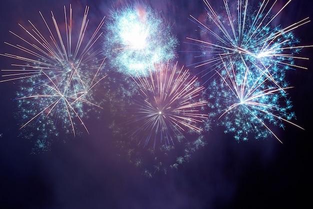 Fogos de artifício coloridos azuis e roxos no fundo do céu negro. celebração do feriado.
