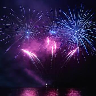 Fogos de artifício coloridos de férias no fundo do céu negro