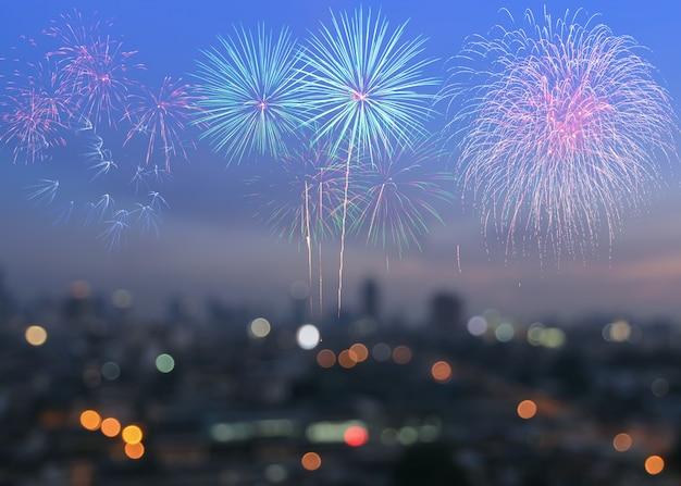 Fogos de artifício coloridos em desfocar o fundo do horizonte da cidade no crepúsculo