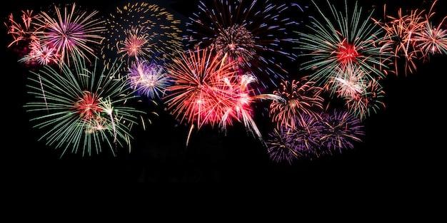 Fogos de artifício coloridos em fundo preto com espaço de cópia na parte inferior