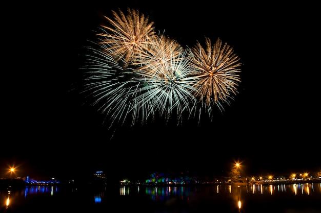 Fogos de artifício coloridos em um fundo de céu noturno.