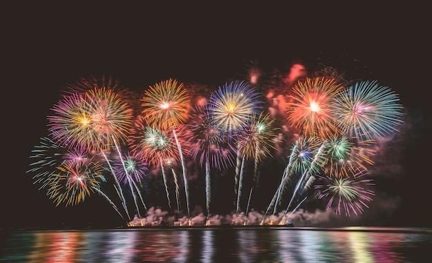 Fogos de artifício coloridos incríveis explodindo para celebração do grande barco sobre o mar, celebração e feliz ano novo e conceito de festival de feliz natal