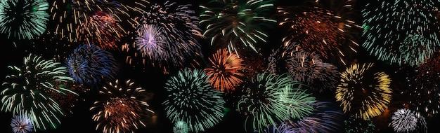 Fogos de artifício coloridos no céu noturno escuro, faixa ampla para plano de fundo de férias