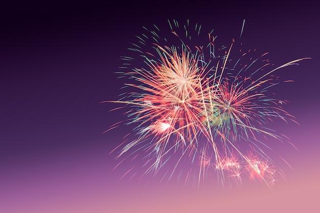Fogos de artifício coloridos no fundo do crepúsculo do sol roxo com espaço de cópia