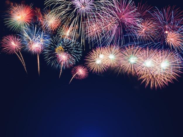Fogos de artifício coloridos sobre o fundo do céu negro com espaço livre para texto