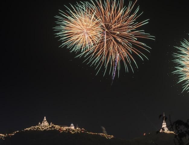 Fogos de artifício coloridos sobre o fundo do céu negro sobre a água