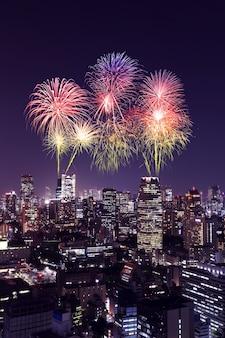 Fogos de artifício comemorando ao longo da paisagem urbana de tóquio à noite, japão