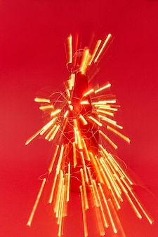 Fogos de artifício de trilhas brilhantes de luzes de natal em uma garrafa de vinho pintada em um fundo vermelho com espaço de cópia. cartão de felicitações de ano novo.