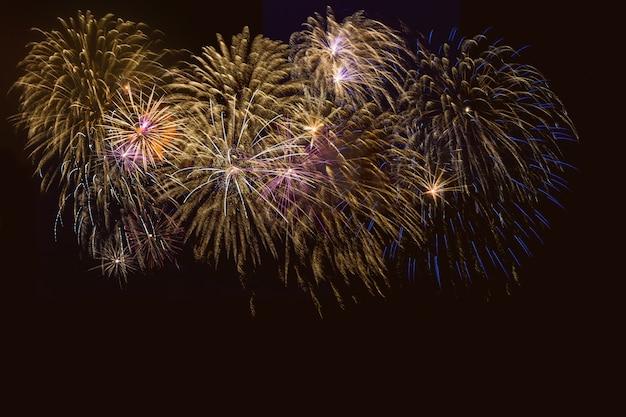 Fogos de artifício dourados, azuis e roxos sobre o céu noturno